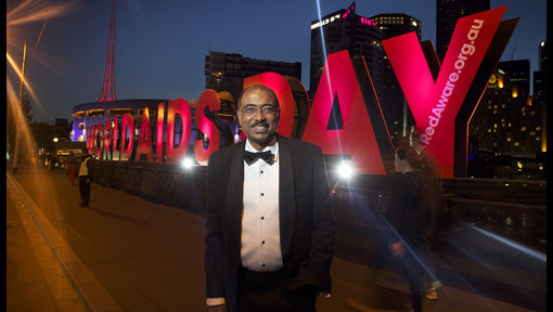 Michel sidibe in front of sign